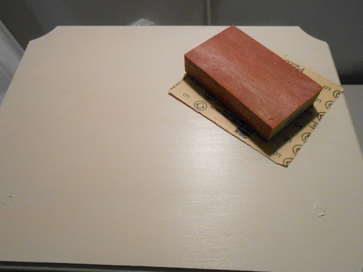 Sanding block and paper on humidifier stand.